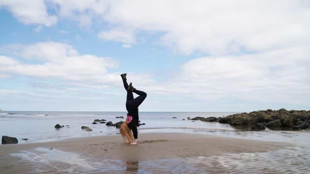 Yoga handstand on a beach